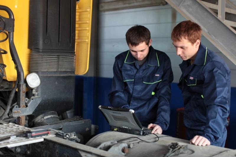 Два специалиста проводят диагностику спецтехники на уникальном оборудовании