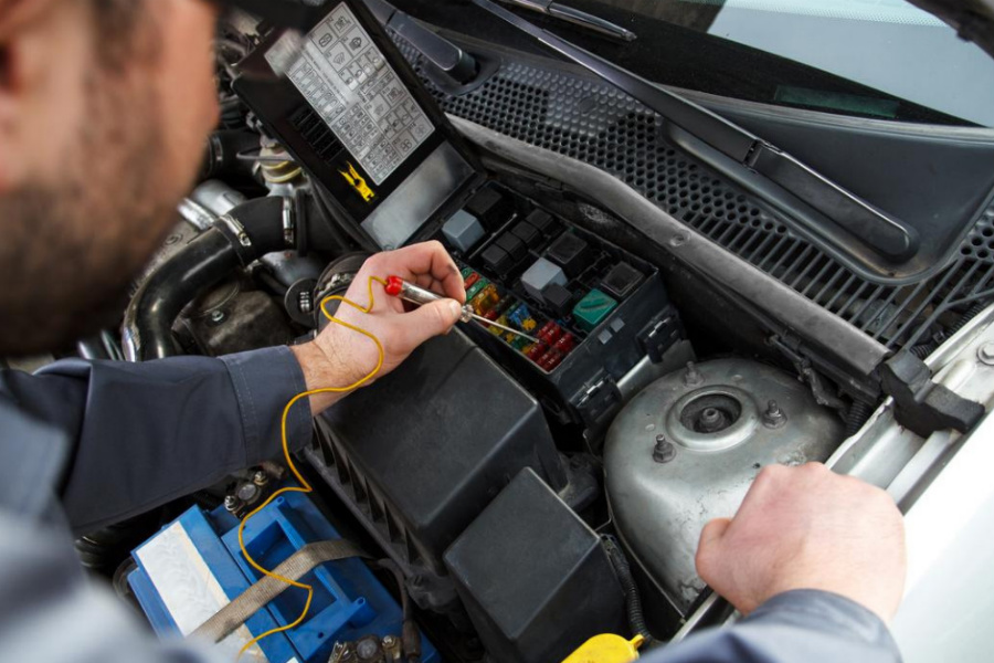 Специалист производит работу по ремонту автоэлектрики грузового авто
